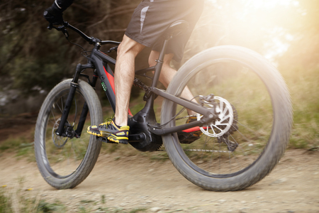 Cropped blurred shot of male rider in action cycling on black electric bike while exercising outdoors in forest. Mountain biker riding booster bicycle with pedal-assist system in woods on sunny day Stock Photo
