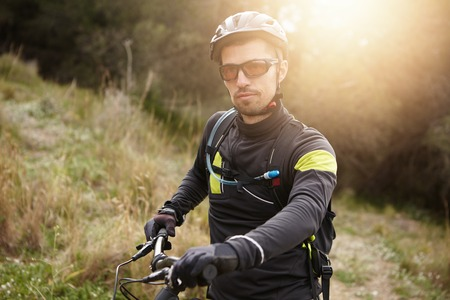 Outdoor shot of handsome young professional mountain biker in helmet, glasses and leather gloves standing outdoors in woods with his electric two-wheeler, getting ready for freeride cycling contest