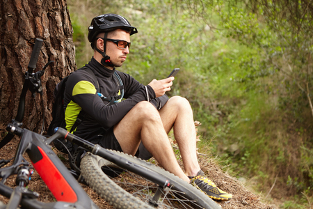 Always in touch. Confident male cyclist typing message or searching for GPS coordinates on smart phone, sitting on grass under big tree while cycling in woods, his e-bike lying on ground next to him Stock Photo - 75993352