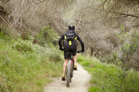 Rear view of unrecognizable young man wearing protective helmet, sports clothes and backpack speeding along forest trail on his two-wheeled motor-powered booster vehicle with pedal-assist system