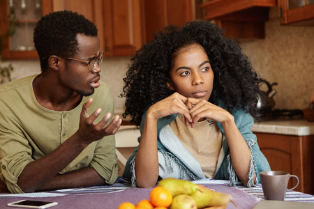 Why did you do this to me? Indignant depressed young Afro-American male in glasses trying to have conversation to his indifferent wife who cheated on him. Relationships problems and infidelity