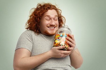 Happy young fat obese man smiling joyfully, keeping eyes closed rejoicing at glass jar of goodies, cant wait to start eating unhealthy but so tasty sweets while keeping strict vegetable diet