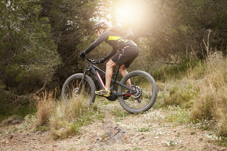 People, sports, active lifestyle and extreme. Professional rider wearing cycling clothing, protective gear and backpack making biking stunts on his mountain electric bike on sunny day. Flare sun Stock Photo