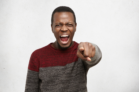 This is your fault. Aggressive angry dark-skinned male shouting and pointing his index finger at camera, having mad furious look, blaming someone. Negative human face expressions and emotions Stock Photo