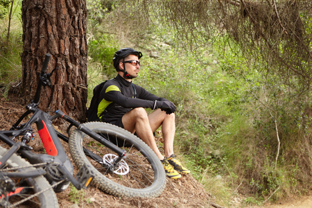 Attractive young European rider in protective gear sitting on the ground at tree, contemplating amazing wild nature around him while having rest after intensive cycling workout in forest on his e-bike Stock Photo - 75993383