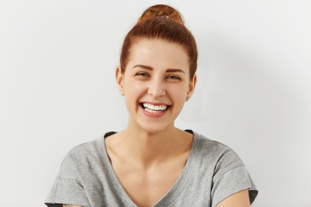 laughing out loud: Headshot of good-looking emotional young Caucasian woman with hair knot, squinting eyes while laughing out loud, happy with good positive news, smiling broadly, showing her straight white teeth
