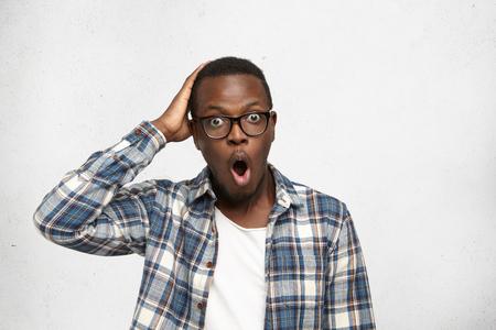 Libero professionista afroamericano maschio bug-eyed in camicia avendo espressione faccia smemorata toccando la testa con la mano, rendendosi conto oggi è la scadenza del suo progetto, aprendo la bocca come se dire di no! Archivio Fotografico - 75999029