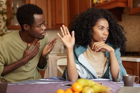 S'il vous plaît, pardonnez-moi. Malheureux tricheur homme afro-américain tenant la main sur sa poitrine présenter des excuses à la femme belle indifférente qui en ignorant et en refusant toutes ses excuses, en lui disant de se perdre Banque d'images - 75999064