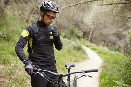 Handsome young European mountain biker in sports wear and protective gear standing on trail in forest with his electric motor-powered bicycle, having small break, drinking water out of plastic tube Banco de Imagens