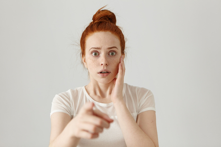 Portrait of scared bug-eyed young redhead female having fearful terrified expression, frightened with something while pointing her index finger at camera. Danger, risk, accusation or recognition