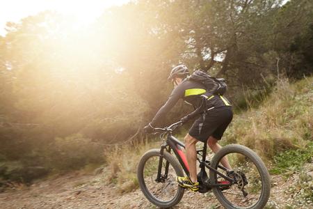 Rear shot of European professional rider in helmet, cycling clothes and eyeglasses riding black electric bike down trail with sun shining ahead of him. People, active healthy lifestyle and extreme