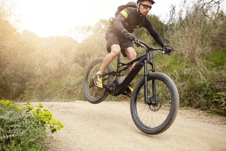 Fietser in actie hoog springen op zwarte elektrische motor aangedreven fiets naar beneden parcours in bos. Jonge ruiter die glazen en helm dragen die extreme biking stunt op e-fiets maken terwijl in openlucht uitoefenend Stockfoto