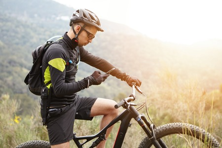 People, sports, active lifestyle and modern technology. Outdoor picture of cyclist on booster bike using navigator on smart phone, exploring map and searching GPS coordinates while biking in mountains Banco de Imagens