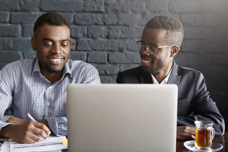 People, business, teamwork and cooperation concept. Two African American corporate workers in formal clothing working together on common presentation on generic laptop computer in modern office