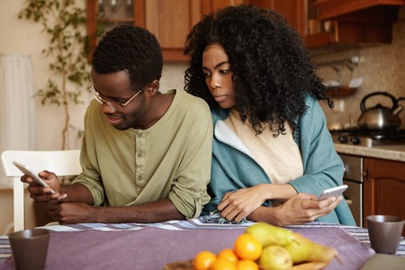 Young African American couple using electronic gadgets at home: happy husband browsing newsfeed via social networks while his jealous possessive wife spying, trying to see whose pictures he is liking Stock Photo