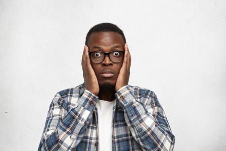 Menselijke emoties en gezichtsuitdrukkingen. Afrikaans manmodel in bril, terloops gekleed, poseren voor populaire tiener magazine, het maken van verschillende gezichten. Dat gevoel toen je de datum van haar verjaardag was vergeten Stockfoto