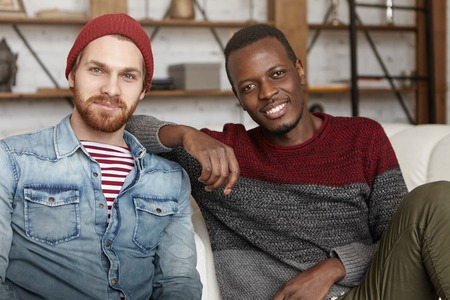 Interracial friendship concept. Happy African American male in casual sweater resting elbow on his best friends shoulder while sitting on white couch at coffee shop, talking and having fun together