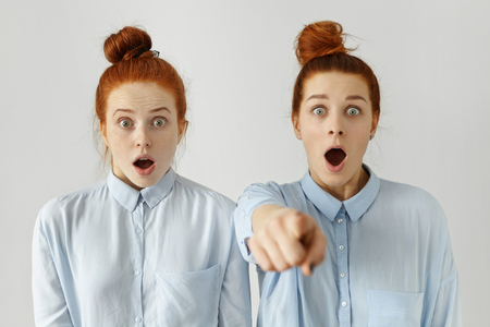 they are watching: Funny frightened sisters wearing identical hair knot and light-blue shirts having shocked looks, scared with horror movie they watching together at home, one of girls pointing finger at camera