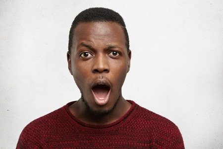 Surprised emotional young black man having stuuned fascinated look, opening mouth widely and raising eyebrows, shocked with big sale prices, standing isolated against blank studio wall background Stockfoto