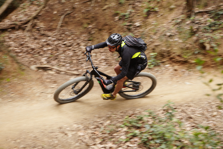 Motion picture of young Caucasian professional rider in helmet, glasses and sportswear speeding down forest trail on booster bike duing intensive workout while preparing for cycling competition Stock Photo