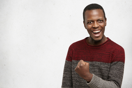 Happy successful lucky young dark-skinned man in warm sweater smiling joyfully, cheering, feeling excited about winning lottery, gesturing with hand, saying: Yes, I made it. Success, luck and victory Stock Photo