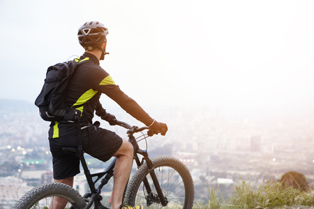 Rear shot of young rider standing on top of hill with booster bike and looking down at foggy city while biking in the morning. Cyclist in black and yellow sports clothes admiring beautiful view Stok Fotoğraf