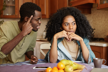 Couple having dispute. Annoyed beautiful dark-skinned female sitting at kitchen table, ignoring screams and insults from her mad furious husband who is shouting at her, holding finger at his temple Stockfoto