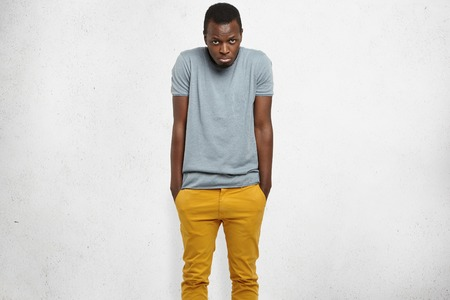Shy handsome young African American man feeling embarassed or uncomfortable, shrugging shoulders, keeping hands in pockets of his mustard jeans, looking at camera with unhappy expression, pouting