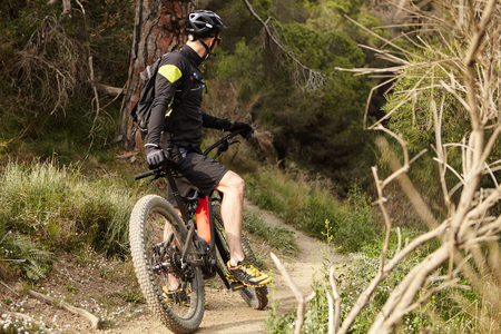 Spending Sunday morning outdoors. Unrecognizable young mountain biker in black cycling clothing keeping foot on pedal of two-wheeled electric vehicle while standing on trail in forest having a break Stock Photo