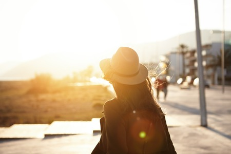 People, travel, holidays and adventure concept. Rear view of young woman with long loose hair walking on city street at sunset wearing hat and coat, enjoying happy pleasant moment of her vacations