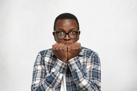 Strong human emotions and feelings. African American guy watching games feeling nervous, panic and shocked, supporting favorite team. Bug-eyed man wearing glasses against white wall with copy space Stock Photo