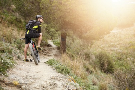 Rear view of cyclist standing on trail in forest with his motor-power e-bike resting during workout outdoors, feeling connected to nature, watching how sun goes down, thinking of his life. Flare sun Stok Fotoğraf