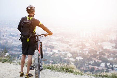 Unrecognizable European male cyclist relaxing on top of mountain, keeping hands on handlebar of his electric pedal-assist bicycle, enjoying amazing urban landscape below. Travel and active lifestyle