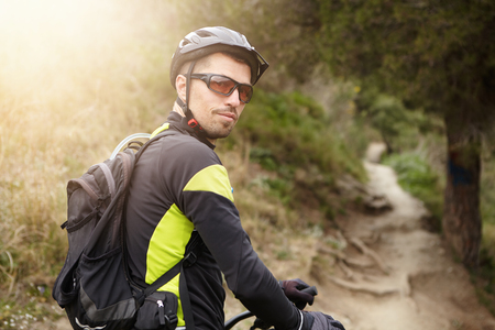 Enjoying active lifestyle and extreme. Happy young Caucasian rider in cycling clothing and protective gear relaxing during workout in woods, turning round and looking at camera with joyful smile