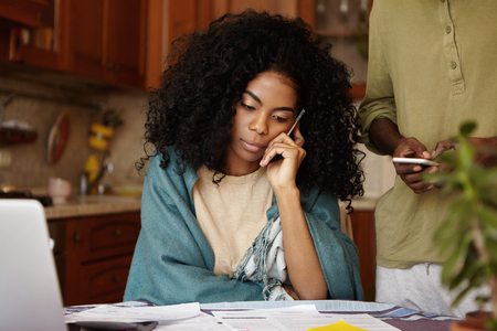 Candid shot of attractive young African woman in plaid talking on mobile phone while paying bills online and calculating family budget, sitting at kitchen table. Family and financial problems concept