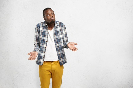 Studio shot of fashionable clueless Afro-American man having confused and dazed look, shrugging shoulders and screwing mouth, standing isolated at blank wall with copy space for your advertisement