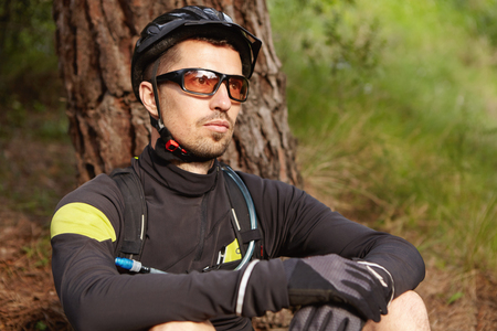 Few minutes of rest. Close up shot of handsome cyclist with beard relaxing after workout, sitting under tree, wearing cycling clothing, gloves, glasses and helmet enjoying fresh air in forest or park