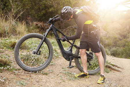 Outdoor shot of professional rider wearing cycling clothing and protective gear during workout in woods, making settings on control panel on his booster motor-powered bicycle before climbing mountain Stock Photo