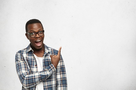 Young amazed African American in glasses looking at camera with opened mouth showing teeth, pointing his finger at white background with copy space for your advertisement or promotional information