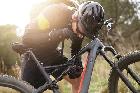 Candid view of male cyclist in sportswear, protective helmet and glasses fixing his motor-powered electrobike that he broke during freeride in woods. Rider repairing his booster bicycle outdoors
