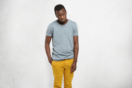 Im so sorry. Cropped portrait of attractive African male in casual t-shirt and mustard pants, looking at camera with guilty expression, apologizing and asking to forgive him for making mistake