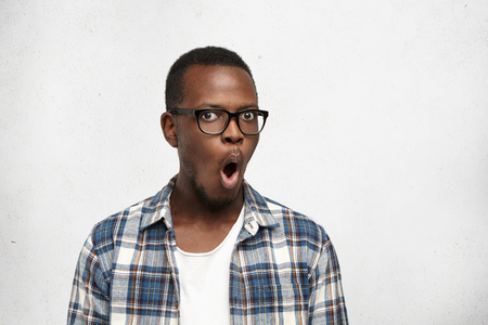 Attractive dark-skinned college student wearing trendy glasses in black frame isolated on white background with copy space for your information, looking shocked, with mouth opened for saying: No way! Stock Photo