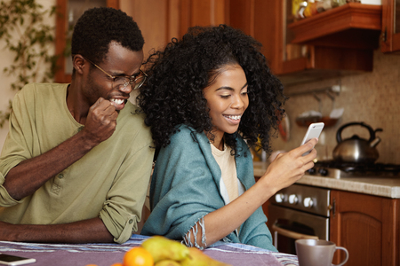 Furious and jealous African American man clenching fist in anger and fury while catching his cheating girlfriend as she messaging her lover on mobile phone having happy and cheerful expression Stockfoto