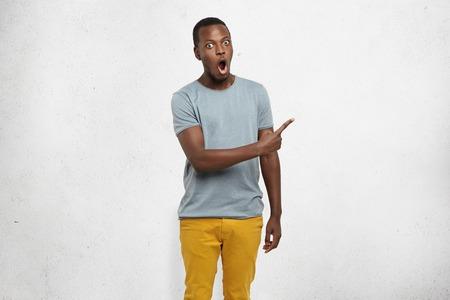 魅力的な面白いショックを受けた若い浅黒い男性には、さりげなくグレーの空白の壁を彼の人差し指を横を指してそれを驚異的な何かを示す服を着
