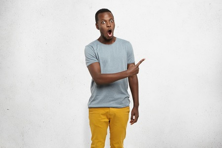 Attractive funny shocked young dark-skinned male dressed casually pointing his index finger sideways at grey blank wall, showing something astonishing on it. Human facial expressions and emotions