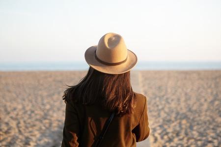 fmale: Back view of European woman in hat and coat going towards sea on boardwalk in fresh spring evening, feeling lonely, missing ex-boyfriend. Unrecognizable fmale traveler walking alon on sandy beach