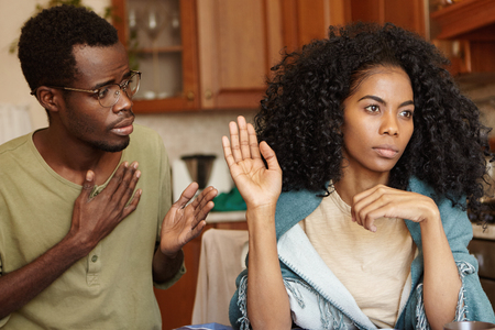 Stop lying to me. Angry beautiful Afro-American girl feeling mad at her unfaithful husband, ignoring his excuses, not believing in lies. Young couple going through hard times in their relationships Stock Photo