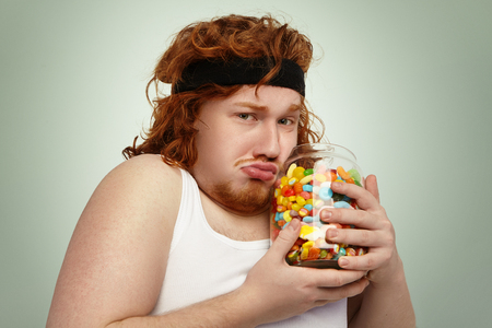 Overweight European male wearing fitness hairband and tank top after intensive cardio workout, trying hard to fight excess weight, looking unhappy, holding big jar of forbidden candies in his hands
