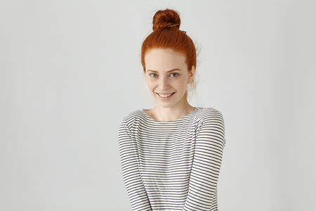 Happy cheerful European teenage girl with ginger hair knot wearing striped long-sleeved t-shirt looking at camera, having joyful look, smiling broadly, enjoying good day and free time indoors