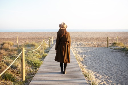 Rear view of fashionable girl with loose dark hair standing alone on boardwalk heading to the sea. Unrecognizable young female in hat and coat came to ocean to clear head while facing stress at work Stockfoto